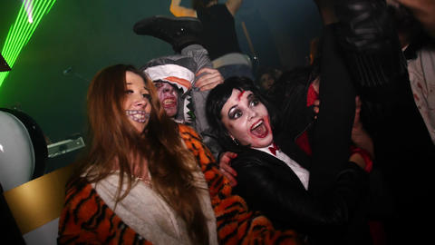 People in costumes have fun at Halloween party in club. Tiger girl, vamp, shark Footage