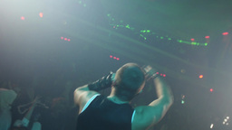 Back side of rap artist perform on stage at Halloween party in crowded club Footage