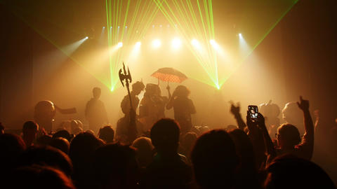 Silhouettes people in costumes at stage of crowded nightclub at Halloween party Footage
