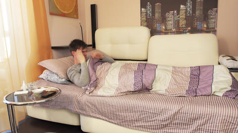 Sick man lying in bed and having headache Live Action