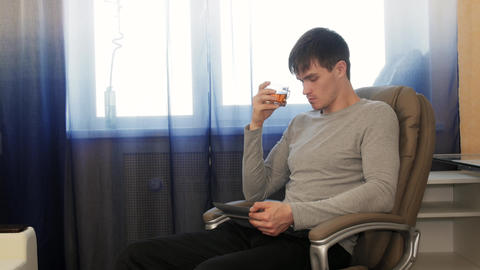 Man With Tablet Pc Sitting On Chair, Drinking Tea stock footage