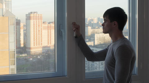 Man in glass home takes a look at view outside Footage