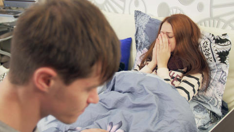 Husband takes care of sick wife with fever in bed Footage