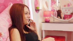 Woman lies on pink bed and says goodbye on phone Footage