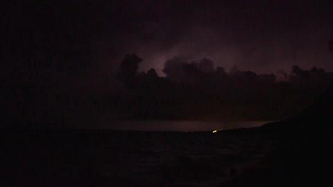 Lightning storm at night along beach shoreline Footage