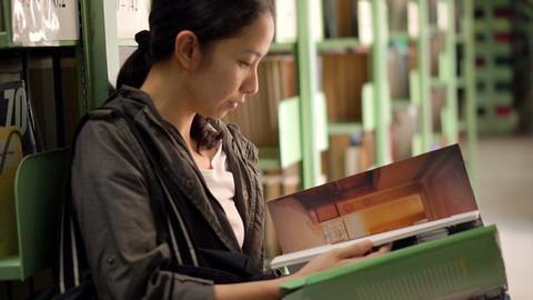 Student girl sitting beside bookshelves and reading books Footage
