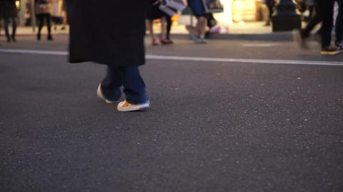 Detail view of feet of Walking people at shopping street in evening Footage