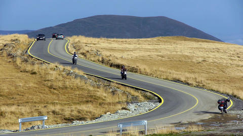 Bikers descend on a road serpentines among other vehicles 109b Footage