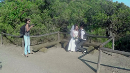 photographer takes pictures of the bride and groom sitting on a wooden bench Footage