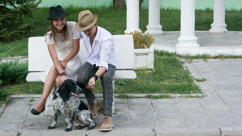 young man and woman in hats stroking dog Footage