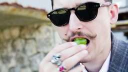 a young man with a mustache eats green grapes Footage