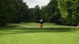 Woman playing a drive at a golf course Footage