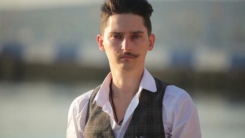 a young man with a mustache looking at you Footage