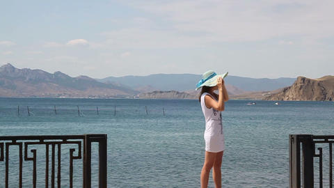 Young Woman In A Hat On The Embankment Against The Sea stock footage