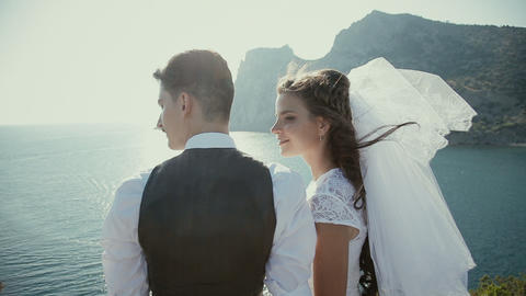 beautiful gorgeous bride and stylish groom kissing on rocks Footage