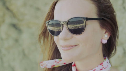 young woman in sunglasses looks pretty sea Footage