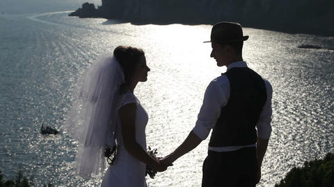 silhouette of a bride and groom on the background of the brilliant sea Footage