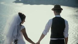 The Bride And Groom On A Cliff Above The Ocean, Holding Hands stock footage