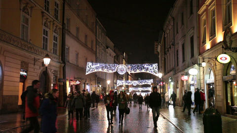 People go on the evening street of Krakow decorated by Christmas Footage