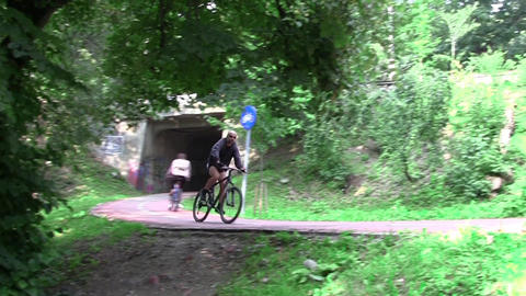 Cyclists in speed on a track landscaped in the woods 01a Footage