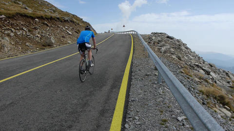 Lone cyclist climbing a slope paved road 96 Footage