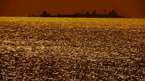 Sparkling water surface and Vessel Ship,horizon,skyline,sunrise,Gold Footage