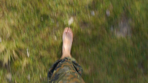 Military walks barefoot on the grass on the mountain pastures 41d Footage