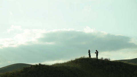 the man photographs the girl on a hill in the wind Footage
