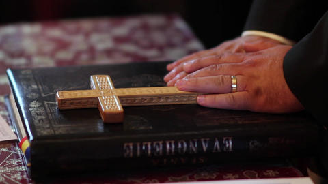 A groom holding their hands to a cross and a Bible , to religious ceremony in ch Footage