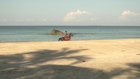 Ngwe Saung, boy riding horse along the sea in slow motion Footage
