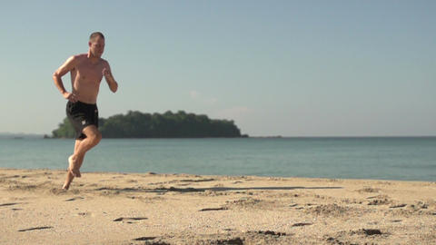 Ngwe Saung, man is running along the beach in slow motion Footage