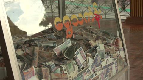 Pathein, Person throws money into donation box at Shwemokehtaw Pagoda Footage