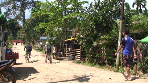 Pathein, Tourists cycling through village Live Action
