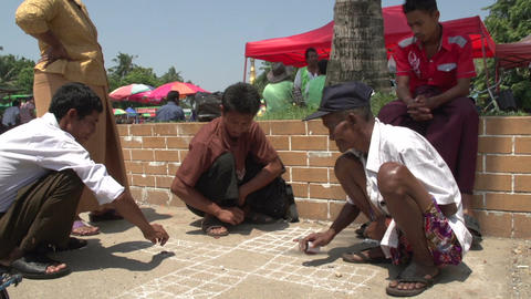 Yangon, men playing dice game on the ground Footage