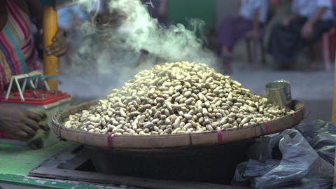 Yangon, baking peanuts at stall Footage