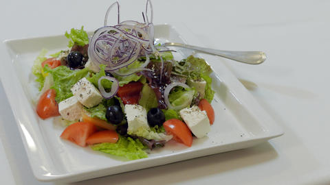 Waiter Puts A Plate With Greek Salad On A Table Footage