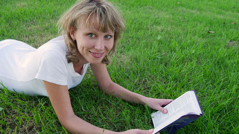 Young woman sitting on the grass and reading a book. Tracking shot Footage