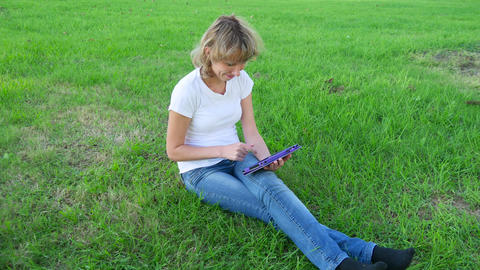 Girl with a tablet computer sitting on the grass Footage