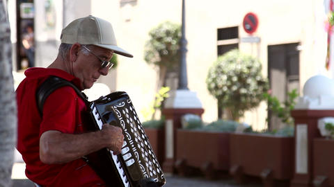 Older man playing on a accordion Live Action