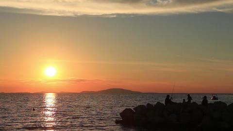 Perfect sea sunset, man fishing on jetty, family, beautiful nature Footage
