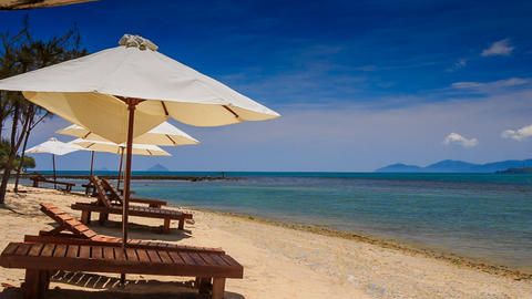 beach umbrellas chairs on gold sand against azure sea Footage