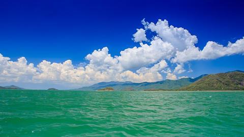 gleams of azure sea distant islands sky cumulus clouds Footage
