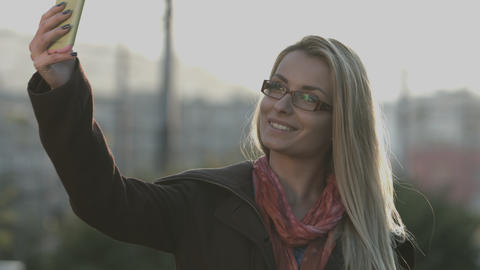 Attractive young woman taking a selfie of herself with her smart phone Footage