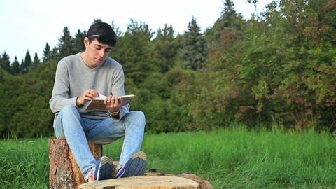 Young Man Sitting In A Park And Reading A Book stock footage