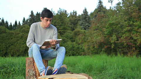 Young man sitting in a park and reading a book Footage