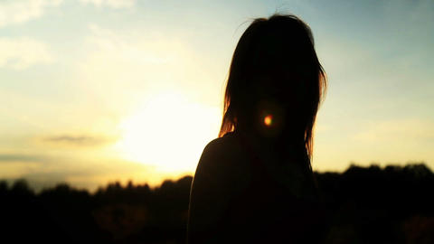 A silhouette of a woman on a sunset turns her head and dancing Footage