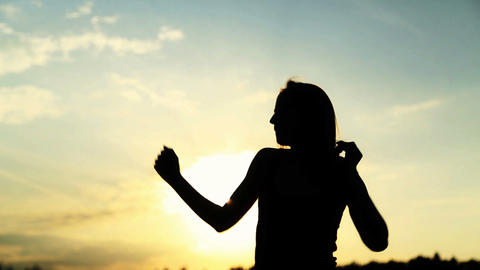 Silhouette of the woman dancing during beautiful sunset. Natural light and darkn Live Action