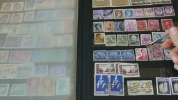 Watching an international stamp collection 2 Footage