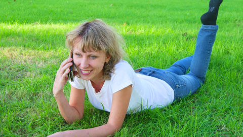 Attractive girl lying on the grass and talking on the phone. Tracking shot Footage