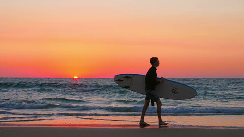 Surfer in silhouette walking with long surf boards at sunset Footage